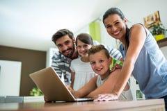 Retrato de la familia feliz usando el ordenador portátil en la sala de estar imagenes de archivo