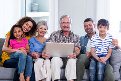 Retrato de la familia feliz usando el ordenador portátil en el sofá Imagen de archivo