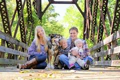 Retrato de la familia feliz y del perro que se sientan en el puente en Autumn Woo Fotografía de archivo