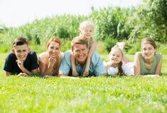 Retrato de la familia grande joven que miente en césped verde al aire libre Fotografía de archivo libre de regalías