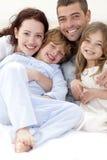 Retrato de la familia joven que miente en cama Imagenes de archivo