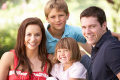 Retrato de la familia joven que se relaja en parque Imágenes de archivo libres de regalías