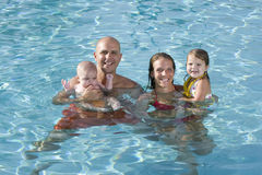 Retrato de la familia joven que sonríe en piscina Fotos de archivo libres de regalías