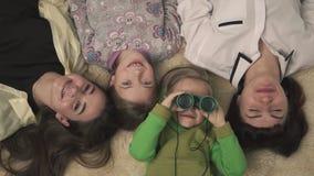 Retrato de la familia de más viejas hermanas alegres y muchacho y una muchacha más jovenes que mienten en la alfombra en el cuart almacen de video