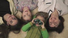 Retrato de la familia de más viejas hermanas alegres y muchacho y una muchacha más jovenes que mienten en la alfombra en el cuart almacen de metraje de vídeo