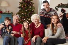 Retrato de la familia multi de la generación que se sienta en Sofa In Lounge At Home el día de la Navidad fotografía de archivo