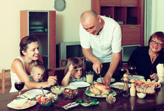 Retrato de la familia multigeneración feliz que come el pollo con los wi Imagenes de archivo