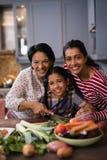Retrato de la familia multigeneración sonriente que prepara la comida en cocina imágenes de archivo libres de regalías