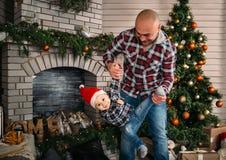 Retrato de la familia de la Navidad del niño pequeño sonriente feliz en el sombrero rojo de santa en manos del ` s del padre Conc Imágenes de archivo libres de regalías
