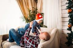 Retrato de la familia de la Navidad del padre sonriente feliz que juega con el pequeño niño en el sombrero rojo de santa Navidad  Fotos de archivo libres de regalías