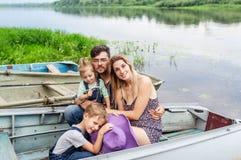 Retrato de la familia de padres con los niños en el barco en el lago hermoso foto de archivo libre de regalías