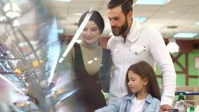 Retrato de la familia que elige el pan y los dulces en la sección de la panadería en supermercado metrajes