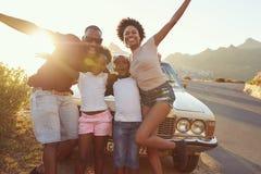 Retrato de la familia que se coloca al lado del coche clásico fotografía de archivo libre de regalías