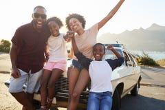Retrato de la familia que se coloca al lado del coche clásico foto de archivo
