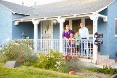Retrato de la familia que se coloca en el pórtico del hogar suburbano foto de archivo