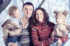 Retrato de la familia que se coloca en fondo del bosque de la nieve del estudio Foto de archivo libre de regalías