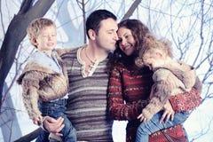 Retrato de la familia que se coloca en fondo del bosque de la nieve del estudio Imagen de archivo libre de regalías