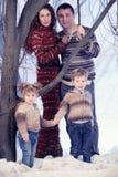 Retrato de la familia que se coloca en fondo del bosque de la nieve del estudio Imágenes de archivo libres de regalías