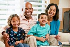Retrato de la familia que se sienta en el sofá junto imagenes de archivo