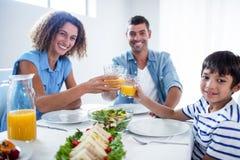 Retrato de la familia que tuesta los vidrios de zumo de naranja mientras que desayunando Imagen de archivo