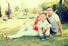 Retrato de la familia sonriente con el muchacho en parque Fotos de archivo libres de regalías