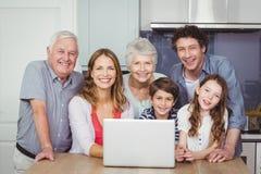 Retrato de la familia sonriente con el ordenador portátil en cocina Foto de archivo