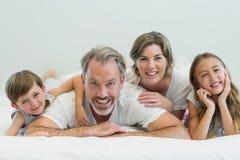 Retrato de la familia sonriente que miente en cama en dormitorio Foto de archivo libre de regalías