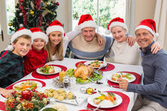 Retrato de la familia sonriente que se sienta junto en la cena de la Navidad Foto de archivo