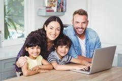 Retrato de la familia sonriente usando el ordenador portátil Imagenes de archivo