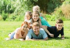 Retrato de la familia vigorosa grande que miente junto en césped verde hacia fuera Fotos de archivo