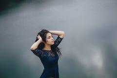 Retrato de la forma de vida de una morenita de la mujer en el fondo del lago en la arena en un día nublado Romántico, apacible, m Foto de archivo libre de regalías