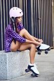 Retrato de la forma de vida del zapato del patinaje sobre ruedas de la mujer que lleva joven al aire libre Imagenes de archivo