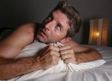 Retrato de la forma de vida del hombre asustado y paranoico atractivo joven que miente en la cama que tiene malos sue?os y pesadi fotos de archivo libres de regalías
