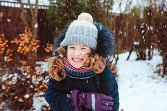 retrato de la forma de vida del invierno de la muchacha feliz del niño que juega bolas de nieve en el paseo Imagen de archivo libre de regalías