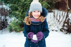 retrato de la forma de vida del invierno de la muchacha feliz del niño que juega bolas de nieve en el paseo Imagen de archivo
