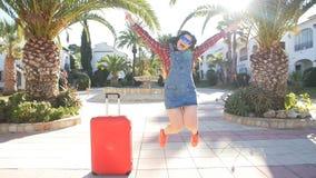 Retrato de la forma de vida del verano de la mujer joven que presenta con la maleta cerca de centro turístico metrajes
