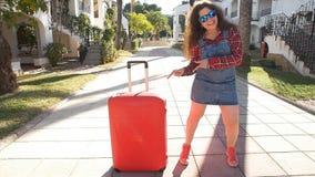 Retrato de la forma de vida del verano de la mujer joven que presenta con la maleta cerca de centro turístico almacen de video
