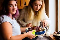 Retrato de la forma de vida de dos mujeres jovenes felices con el pavo cocido para la cena de la acción de gracias Foto de archivo libre de regalías