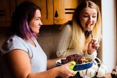 Retrato de la forma de vida de dos mujeres jovenes felices con el pavo cocido para la cena de la acción de gracias Fotografía de archivo libre de regalías