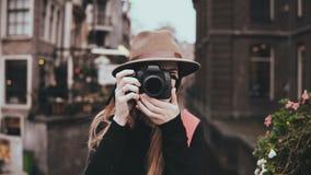 Retrato de la forma de vida Fotógrafo profesional 4K La señora alegre atractiva en sombrero elegante con una cámara toma una imag almacen de metraje de vídeo