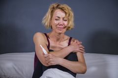 Retrato de la forma de vida de la mujer embarazada desesperada joven que usa la prueba de embarazo triste y deprimida para la esp foto de archivo