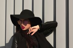 Retrato de la forma de vida de la mujer joven en sombrero y espejo brimmed anchos fotos de archivo