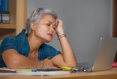Retrato de la forma de vida de la oficina de la mujer asi?tica atractiva madura triste y deprimida que trabaja en el escritorio d imagenes de archivo