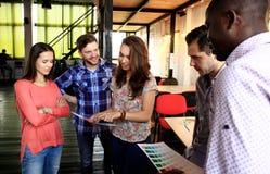 Retrato de la gente joven feliz en una reunión que mira la cámara y la sonrisa Diseñadores jovenes que trabajan junto en a imagenes de archivo