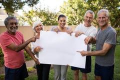 Retrato de la gente mayor sonriente con el instructor que lleva a cabo el cartel en blanco fotos de archivo libres de regalías