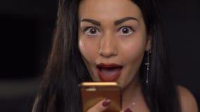 Retrato de la griterío morena atractiva, de la risa y emocionalmente de hablar vía el teléfono móvil almacen de video