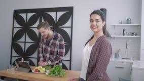 Retrato de la hembra feliz en la cocina, miradas sonrientes de la mujer en masculino para las cuales prepara la comida útil sana  almacen de video