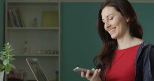 Retrato de la hembra hermosa que habla en el teléfono y que recibe buenas noticias con los papeles en sus manos que sonríen y fel