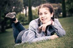 Retrato de la hembra joven mientras que miente en jardín del verde de la primavera Imágenes de archivo libres de regalías