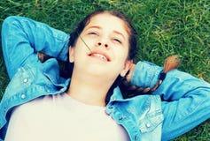 Retrato de la hembra joven mientras que miente en jardín del verde de la primavera Fotografía de archivo